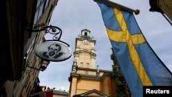 FILE - Sweden's flag is seen near the Stockholm Cathedral in Gamla Stan or the Old Town district of Stockholm, Sweden. For the first time since record-keeping began in 1749, Sweden now has more men than women.