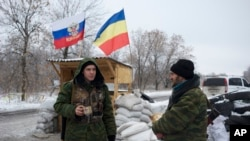 FILE - Pro-Russian rebels, cossacks from the 1st Cossack Regiment, guard a checkpoint decorated by Russian national and Don Cossacks flags, just outside in Pervomaisk, eastern Ukraine, Dec. 6, 2014.