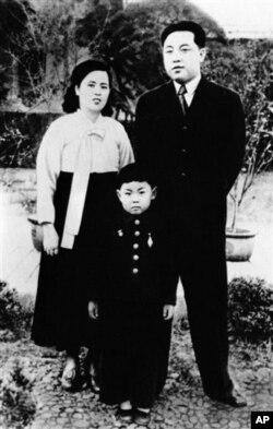朝鮮中央通訊社未註明日期的照片: 金正日(中)童年時期與父母合影。左邊是母親金正淑,右邊是父親金日成。