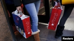 FILE - Shoppers exit Macy's on 34th St. in Herald Square in the Manhattan borough of New York, Nov. 24, 2015.