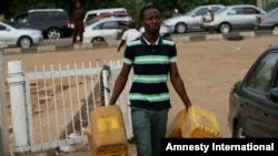 FILE - A man carries empty containers to buy fuel at a petrol station in Abuja, Nigeria.