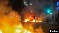 A man stands between bonfires lit by demonstrators as they clashed with police during an anti-government protest in Rio de Janeiro, Brazil, June 20, 2013.
