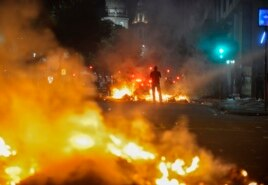 A man stands between bonfires lit by demonstrators as they clashed with police during an anti-government protest in Rio de Janeiro, June 20, 2013.