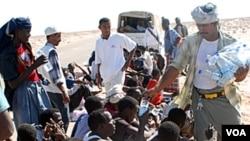 Petugas Bantuan Kemanusiaan mendistribusikan air untuk pencari suaka Somalia setibanya di kampung Hasn Beleid, 230 kilometer dari pelabuhan Aden, Laut Merah (Foto: dok).