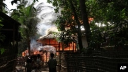 People look on a house engulfed in flames in Sittwe, Burma, June 11, 2012.