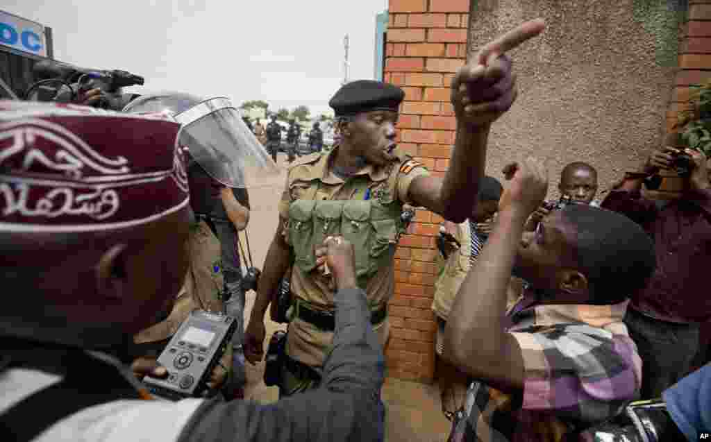A policeman argues with a supporter of opposition leader Kizza Besigye at the gates of his party headquarters in Kampala, Uganda.