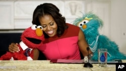 First lady Michelle Obama, center, with PBS Sesame Street's characters Elmo, left, and Rosita, right, as they help promote fresh fruit and vegetable consumption to kids in an event in the State Dining Room of the White House in Washington, file photo.