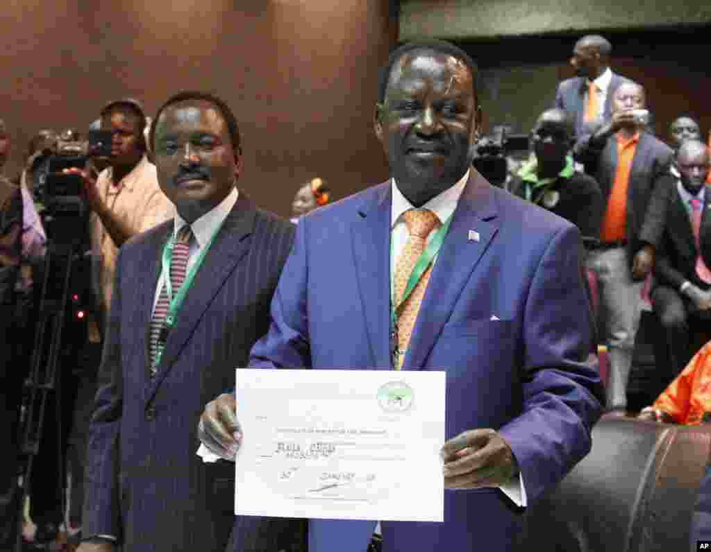 Orange Democratic Party, ODM, presidential candidate, Raila Odinga, right, displays his registration certificate, with running mate Vice President Kalonzo Musyoka, left, in Nairobi, Kenya, Jan. 30. 2013.