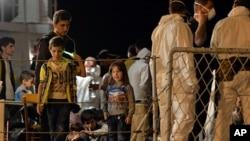 "FILE - Migrants wait to disembark from the Italian Navy Ship ""Grecale"" at Pozzallo harbor, Sicily, May 13, 2014."