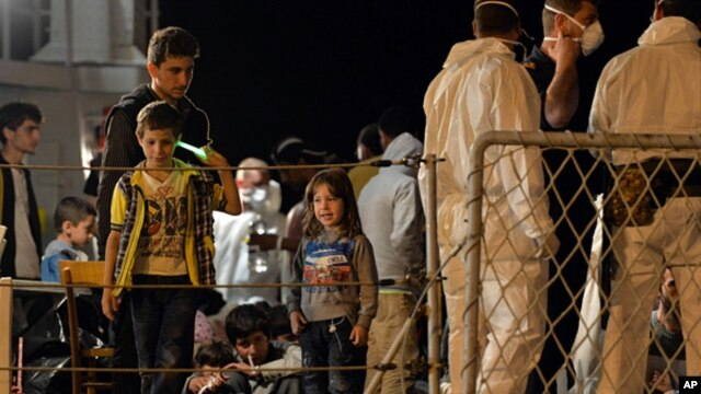 "FILE - Migrants wait to disembark from the Italian Navy Ship ""Grecale"" at Pozzallo harbor, Sicily, May 13, 2014."