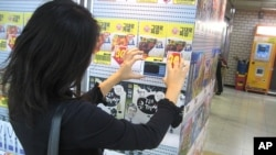 A young woman uses her smartphone to shop for groceries in Seoul's Seolleung subway station.