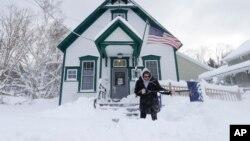 Seorang pegawai membersihkan salju di depan kantor pos di kota Grafton, negara bagian New York, Senin (21/11).