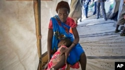 In this Dec. 31, 2013 file photo, Nyanhial, 5, is comforted by her mother as she is treated for fever and vomiting at a Doctors Without Borders medical tent in the Jebel area on the outskirts of Juba, South Sudan. Human Rights Watch says the more than year long conflict has taken a heavy toll on civilians. HRW calls on the AU to release its commission of inquiry report on the conflict. (AP Photo/Ben Curtis, File)