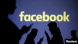 FILE - Silhouettes of mobile users are seen next to a screen projection of Facebook logo in this picture illustration taken March 28, 2018.