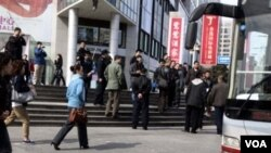 """Para polisi Tiongkok menangkapi jemaat gereja """"tak terdaftar"""" dan memasukkan mereka ke dalam bis di Beijing (10/4)."""