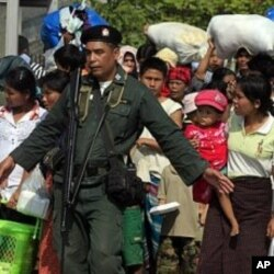 Thai police escort a group of Burma refugees crossing to Myawaddi town at the Thai-Burma border town of Mae Sot (File Photo)