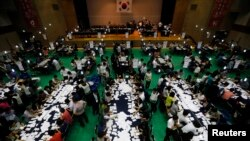 Election officials count the ballots for local elections in Seoul, June 4, 2014.