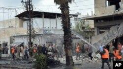 Pasukan Keamanan Suriah dan petugas pemadam kebakaran berkumpul di lokasi ledakan di pusat kota Homs, Suriah, 23 Mei 2017 (Sana via AP).