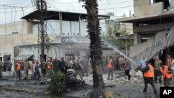 FILE - Syrian security forces and firefighters gather at an explosion in the central city of Homs, Syria, May 23, 2017. Syrian state TV reported that an explosion in the central city of Homs has killed several people.