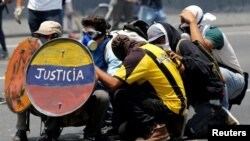 "FILE - Opposition supporters use a shield that reads ""Justice"" as they clash with security forces during a rally against Venezuela's President Nicolas Maduro in Caracas, Venezuela, April 26, 2017."
