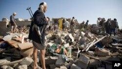 Pemberontak Houthi memeriksa bangunan perumahan yang hancur akibat serangan udara Saudi di dekat bandara Sanaa, Yaman, Kamis (26/3).