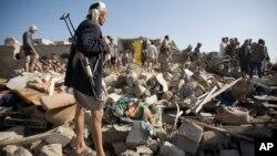 Một phiến quân Houthi đứng canh trong khi dân chúng tìm kiếm người sống sót sau các vụ oanh kích của Ả-rập Saudi 26/3/15