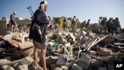 26일 사우디아라비아가 예멘 후티 반군을 겨낭한 공습을 단행한 후 사나 공항 인근 건물들이 무너졌다. 후티 반군이 수색 현장을 지키고 있다.