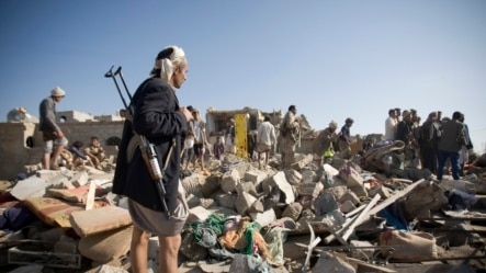 យុទ្ធជនក្រុមឧទ្ទាម ហ៊ូធី (Houthi) និកាយ Shi'ite ឈរល្បាតនៅស្របពេលដែលប្រជាជនស្វែងរកអ្នកនៅរស់នៅក្រោម កម្ទេចលំនៅដ្ឋានដែលត្រូវបានបំផ្លាញដោយការវាយប្រហារតាមអាកាសដោយអារ៉ាប៊ី សាអួូឌីត។