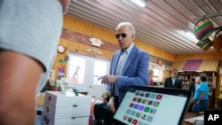 President Joe Biden makes a purchase at the King Orchards fruit farm Saturday in Central Lake, Mich., July 3, 2021.
