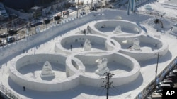 FILE - Visitors tour near the snow sculpture in the shape of the Olympic rings displayed at the Daegwanryung Snow festival in Pyeongchang, South Korea, Feb. 3, 2017.