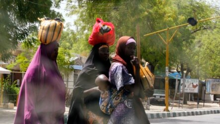 Women attempt to cross Jos Road with their belongings, after the military declared a 24-hour curfew over large parts of Maiduguri in Borno State May 19, 2013.