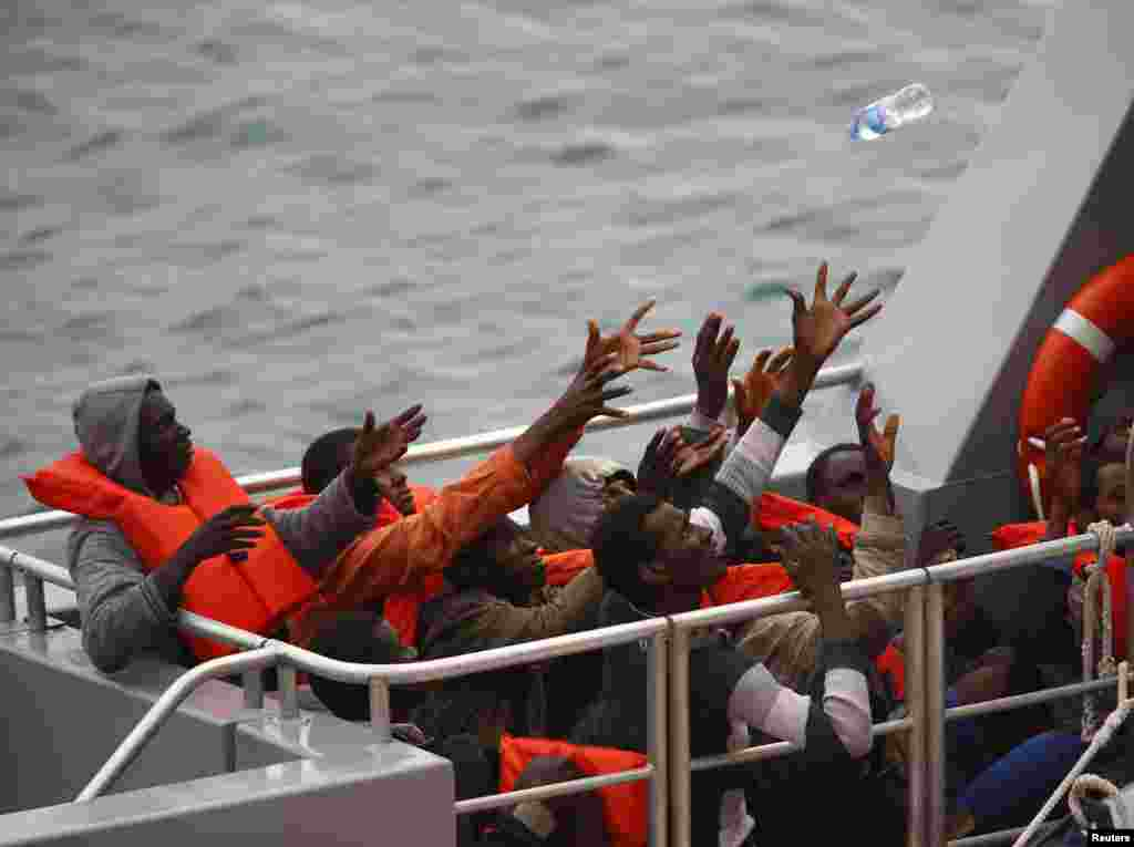 Rescued migrants on the deck of an Armed Forces of Malta (AFM) patrol boat reach out for a bottle of water after arriving at the AFM's Maritime Squadron base at Haywharf in Valletta's Marsamxett Harbor. A Maltese patrol boat rescued about 80 migrants off the island, but another 20 people were feared to have died.