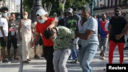 Plain clothes police detain a person during protests against and in support of the government, amidst the coronavirus disease (COVID-19) outbreak, in Havana, Cuba July 11, 2021.