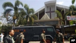 Indonesian police officer stands guard near an armored vehicle outside a church after an explosion in Solo, Central Java, Indonesia, Sunday, Sept. 25, 2011. A suicide bomber attacked the church packed with hundreds of worshippers Sunday, killing himself a