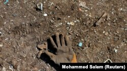 A glove left behind by a Palestinian worker is seen on the ground at a metal waste junkyard. The picture was taken January 25, 2021. REUTERS/Mohammed Salem