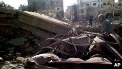 Dalam foto yang dirilis oleh kantor berita Suriah, SANA, seorang warga Suriah memeriksa lokasi kejadian ledakan bom bunuh diri di Qamishli, 800 kilometer bagian timur laut Damaskus, Suriah (30/9).