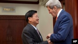 Lao Foreign Minister Thongloun Sisoulith, left, welcomes U.S. Secretary of State John Kerry, before their meeting at the Ministry of Foreign Affairs in Vientiane, Laos, Monday, Jan. 25, 2016. Kerry is in Laos on the third leg of his latest round-the-world diplomatic mission, which will also take him to Cambodia and China. (AP Photo/Jacquelyn Martin, Pool)