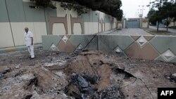 Giới chức Libya đứng cạnh một hố bom sau vụ không kích vào căn cứ Bab al-Azizia của lãnh tụ Gadhafi ở Tripoli, ngày 1/6/2011