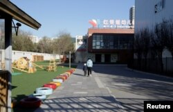 A child walks with a parent at the kindergarten run by pre-school operator RYB Education Inc being investigated by China's police, in Beijing, Nov, 24, 2017.
