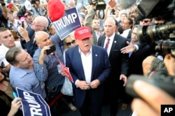 Republican presidential candidate Donald Trump, center, greets supporter after speaking at a campaign event in Los Angeles, Sept. 15, 2015.