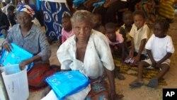 Women receive mosquito nets to fight malaria.