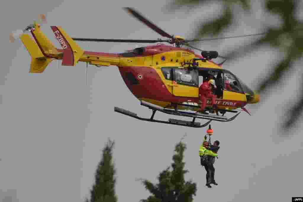 جنوبی فرانس میں طوفان اور سیلاب سے متاثر علاقے میں ایک شخص کو امدادی ہیلی کاپٹر کے ذریعے اٹھایا جارہا ہے۔ گزشتہ شب طوفان سے چھ افراد ہلاک ہوئے