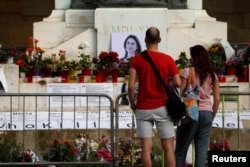 People look at the makeshift memorial to assassinated anti-corruption journalist Daphne Caruana Galizia on the Great Siege Monument after the police blocked off access to it, in Valletta, Malta, April 22, 2018.