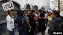 Una mujer de la tercera edad se identifica como la última de la fila para hacer compras en un supermercado del gobierno en Caracas.
