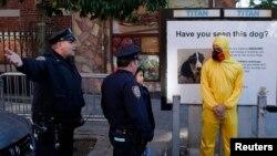 Policías de Nueva York le piden a un hombre en disfraz de Halloween imitando el equipo protector contra el ébola que se aleje del lugar donde vive el Dr. Craig Spencer que ha dado positivo al virus.