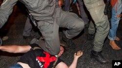 Seorang polisi Israel menindih seorang pedemo dalam unjuk rasa menentang Perdana Menteri Israel Benjamin Netanyahu di luar kantornya di Yerusalem, 22 Juli 2020.