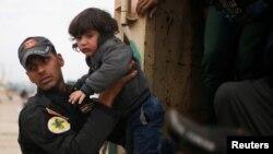 28일 이라크 모술에서 군인들이 정부 군과 ISIL 간 교전을 피해 도망하는 난민들을 돕고 있다.