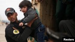 一名伊拉克士兵试图从摩苏尔西部老城的一辆卡车里抱出受伤的孩童(2017年3月28日)