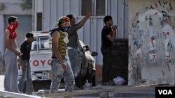 Warga Syiah penghuni desa Malkiya, barat daya Manama, mengawasi polisi anti-huru-hara yang mendekati daerah mereka (31/3).
