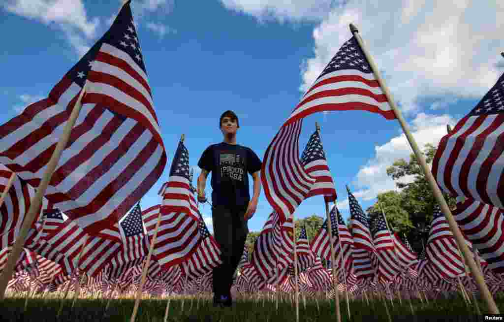 Jackson Tucker walks through the field of 3,000 U.S. flags placed in memory of the lives lost in the Sept. 11, 2001 attacks, at a park in Winnetka, Illinois, Sept. 10, 2016.
